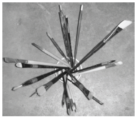 Paint brushes on a table, pointing outwards from a center point